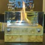 Lareira de Mesa - Largura: 25 cm | Altura: 20 cm | Profundidade: 25 cm | Material: Madeira teca, inox e vidro temperado